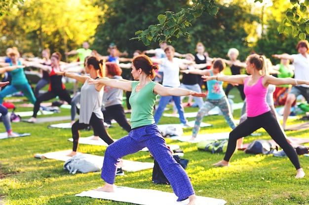 Duża grupa dorosłych uczęszczających na zajęcia jogi na zewnątrz w parku?