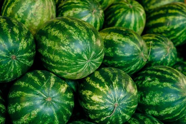 Duża grupa dużych zielonych arbuzów w supermarkecie robiąca kupę, która jest częścią produktów rolnych na wystawie