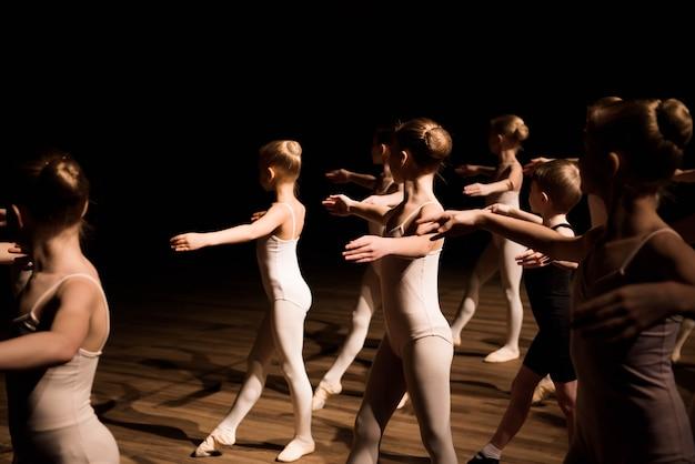Duża grupa dzieci ćwiczących i tańczących balet