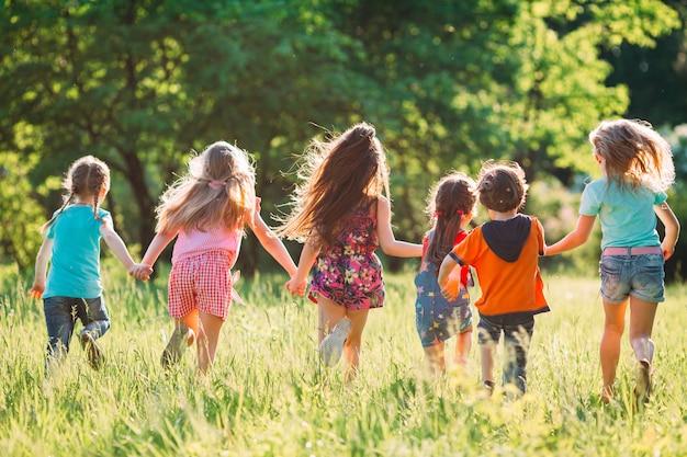 Duża grupa dzieci, przyjaciół chłopców i dziewcząt biegających w parku w słoneczny letni dzień w swobodnych ubraniach.