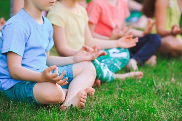 Duża grupa dzieci uprawiających jogę w parku siedzi na trawie.