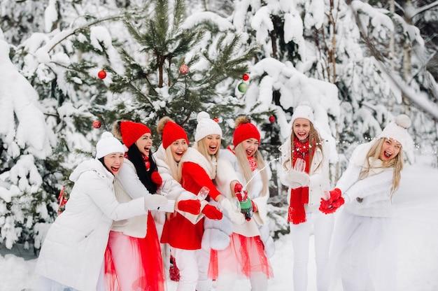 Duża grupa dziewcząt z kieliszkami szampana w dłoniach stoi w zimowym lesie. dziewczyny w czerwono-białych ubraniach z noworocznymi napojami w zaśnieżonym lesie.