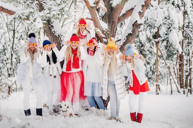 Duża grupa dziewcząt z mandarynkami stoi w zimowym lesie, dziewczyny w czerwono-białych ubraniach z owocami w zaśnieżonym lesie.
