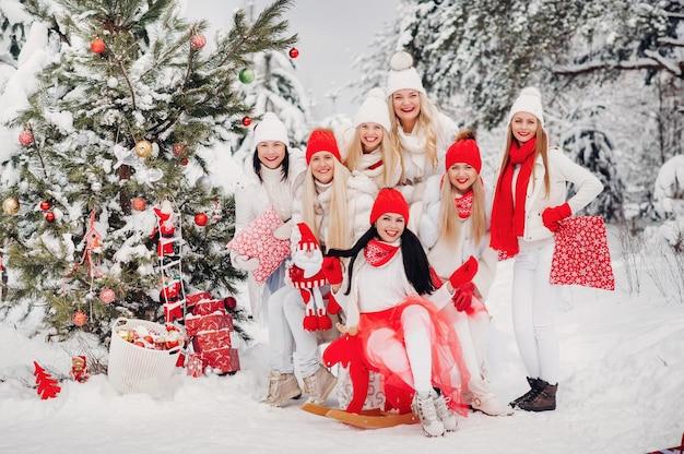 Duża grupa dziewczynek z prezentami świątecznymi w dłoniach stojących w zimowym lesie. dziewczyny w czerwono-białych ubraniach z prezentami świątecznymi w śnieżnym lesie
