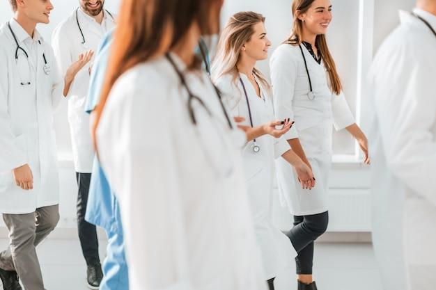 Duża grupa lekarzy krocząca przez hol szpitalny