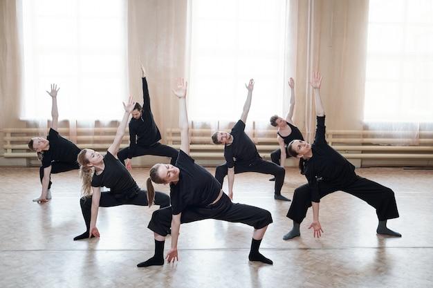 Duża grupa młodych, sprawnych młodych ludzi w czarnej odzieży sportowej ćwicząca razem podczas treningu na parkiecie studia tańca