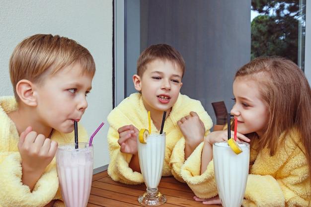 Duża grupa przyjaciół dobrze się bawiąc przy mlecznych koktajlach.