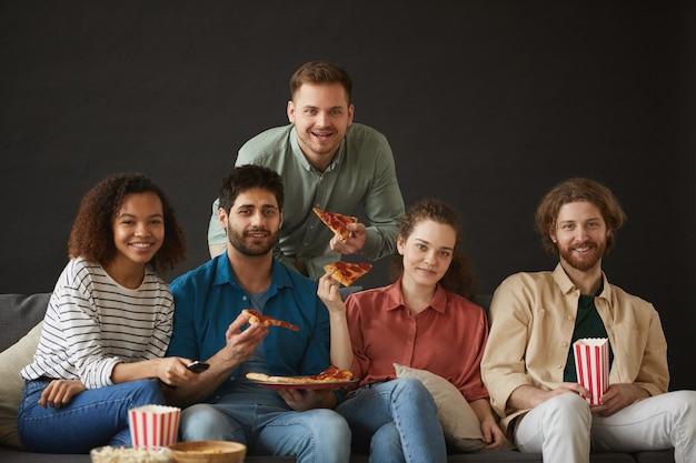 Duża grupa przyjaciół jedząca pizzę i przekąski, ciesząc się imprezą w domu, siedząc na dużej sofie
