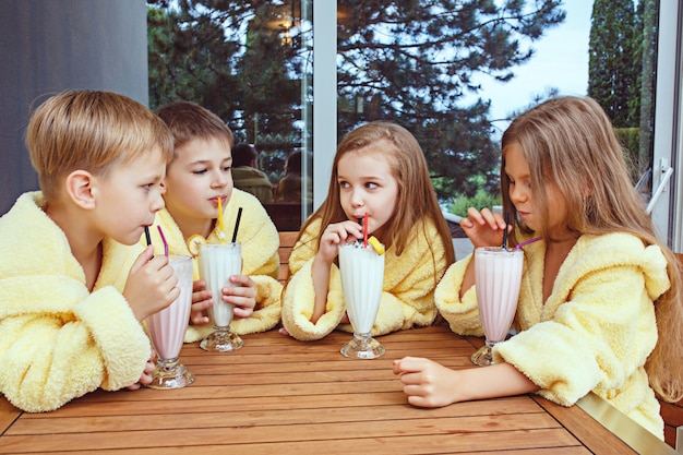 Duża grupa przyjaciół spędzających czas przy mlecznych koktajlach. szczęśliwi uśmiechnięci chłopcy i dziewczęta w żółtych szlafrokach frotte. koncepcja mody dla dzieci