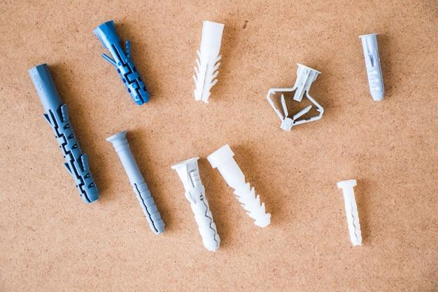 Duża grupa różnych plastikowych kołków ściennych na brązowym tle, widok pod dużym kątem