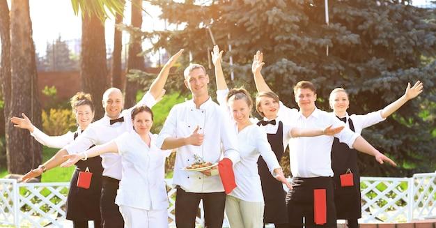Duża grupa szczęśliwych i emocjonalnych kelnerów stojących w rzędzie za sobą
