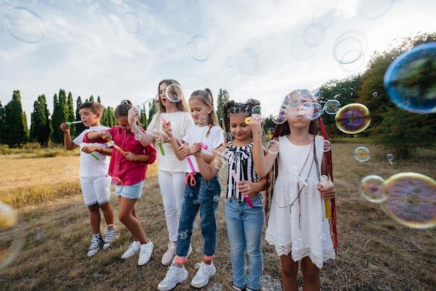 Duża grupa wesołych dzieci bawi się w parku i nadmuchuje bańki mydlane. gry w obozie dla dzieci.