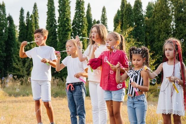 Duża grupa wesołych dzieci bawi się w parku i pompuje bańki mydlane. gry w obozie dla dzieci.