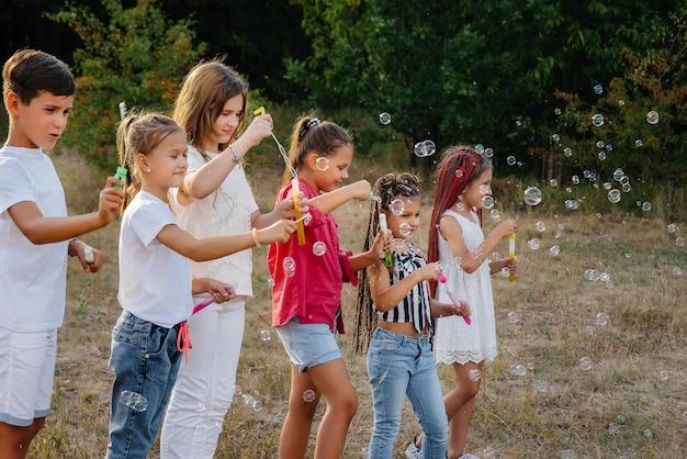 Duża grupa wesołych dzieci bawi się w parku i pompuje bańki mydlane