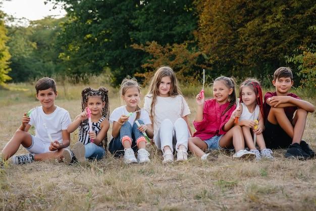 Duża grupa wesołych dzieci siada na trawie w parku i uśmiecha się