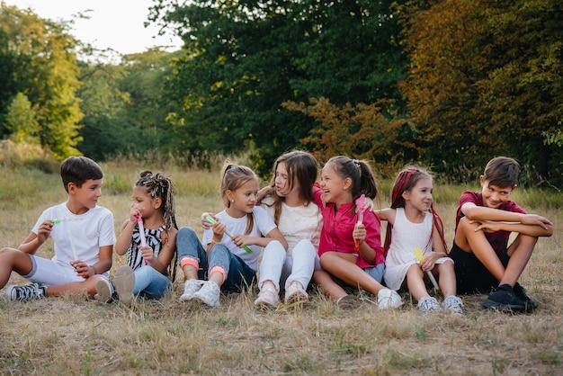 Duża grupa wesołych dzieci siada na trawie w parku i uśmiecha się.