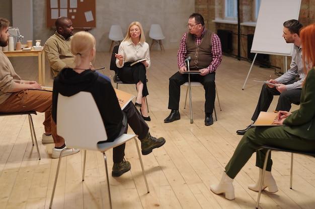 Duża grupa współczesnych osób z problemami psychologicznymi siedzących na krzesłach w kręgu i słuchających dojrzałej blond doradczyni