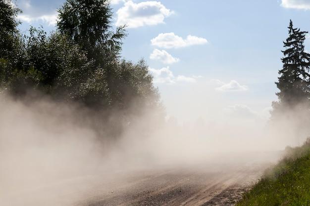 Duża ilość kurzu na jezdni po przejechaniu samochodów, teren wiejski z drogami piaszczysto-żwirowymi bez asfaltu