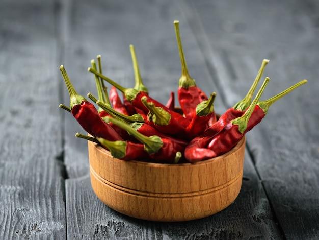 Duża ilość suszonych papryczek chili w drewnianej misce na rustykalnym stole.