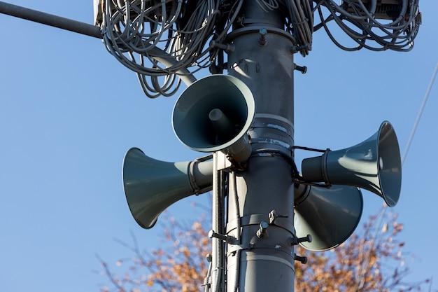 Duża instalacja przemysłowa na słupie z megafonami ostrzegającymi ludność o niebezpieczeństwie, przewody