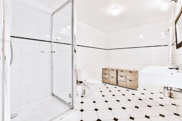 Duża, jasna łazienka z podłogą z płytek w ośmiokątne kropki, białą toaletą i umywalką w jasnym świetle