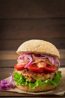 Duża kanapka - burger hamburgerowy z wołowiną, czerwoną cebulą, pomidorem i smażonym boczkiem.