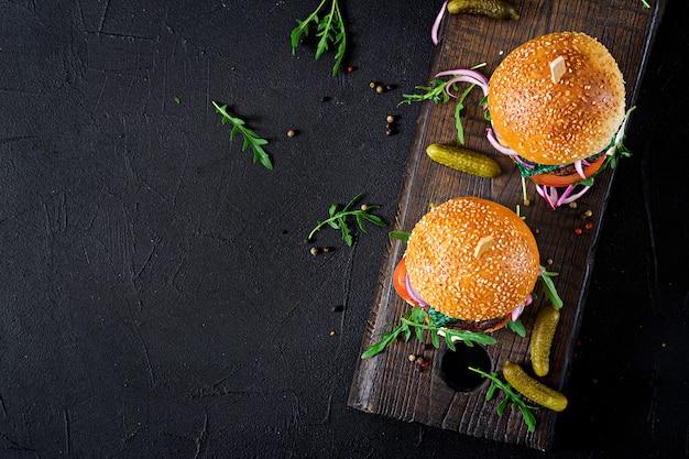 Duża kanapka - burger hamburgerowy z wołowiną, pomidorem, serem bazyliowym i rukolą. widok z góry. płaskie leżało