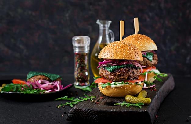 Duża kanapka - burger hamburgerowy z wołowiną, pomidorem, serem bazyliowym i rukolą.
