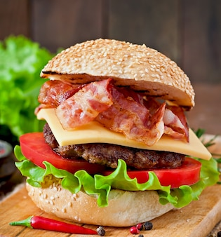 Duża kanapka - burger hamburgerowy z wołowiną, serem, pomidorem i smażonym boczkiem