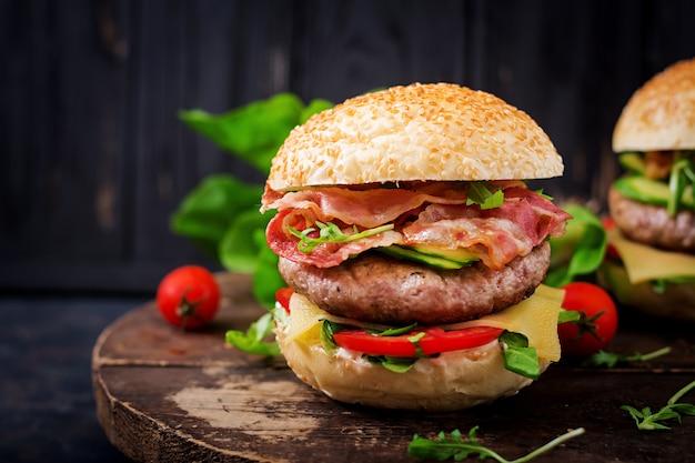 Duża kanapka - burger hamburgerowy z wołowiną, serem, pomidorem, ogórkiem i smażonym boczkiem.