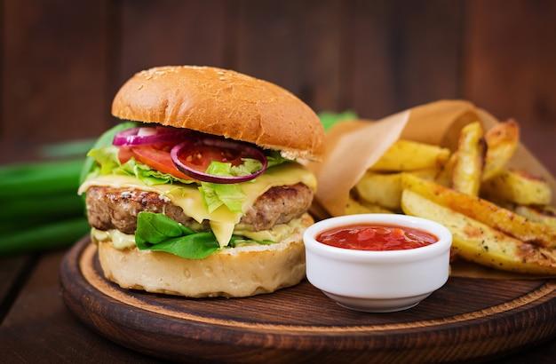 Duża kanapka - hamburger z soczystą wołowiną, serem, pomidorem i czerwoną cebulą