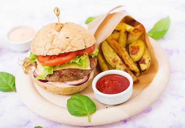Duża kanapka - hamburger z soczystym burgerem wołowym, serem, pomidorem i czerwoną cebulą i frytkami.