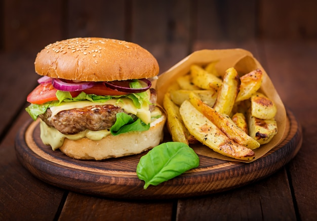 Duża kanapka - hamburger z soczystym burgerem wołowym, serem, pomidorem i czerwoną cebulą na drewnianym stole