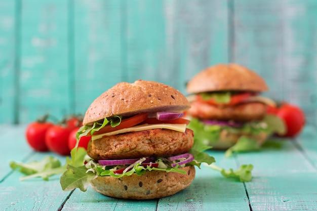 Duża kanapka - hamburger z soczystym kurczakiem, serem, pomidorem i czerwoną cebulą na drewnianym stole