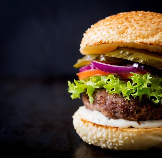 Duża kanapka - hamburger z wołowiną, marynatami, pomidorem i sosem tatarskim na czarnym tle.