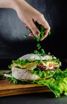 Duża kanapka na czarnym tle street food, fast food. domowe burgery z wołowiną