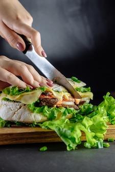 Duża kanapka street food, fast food. domowe hamburgery z wołowiną, serem na drewnianym stole. stonowany image.chef tnie nóż kanapkowy
