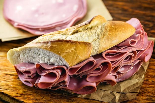 Duża kanapka z chleba z plastrami wieprzowiny zwanej mortadellą