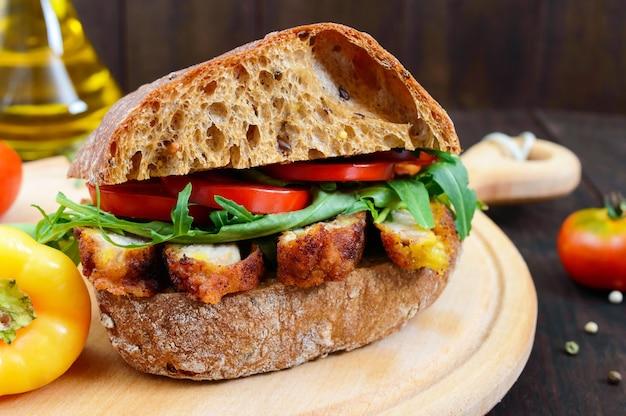 Duża kanapka z kawałkami mięsa rukola pomidor płatki ciabatta