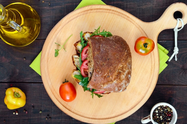 Duża kanapka z kawałkami mięsa, rukolą, pomidorem, ciabattą zbożową na desce do krojenia na ciemnym drewnianym stole