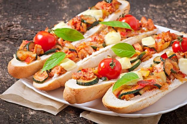Duża kanapka z pieczonymi warzywami (cukinia, papryka, pomidory) z serem i bazylią na starym drewnianym tle