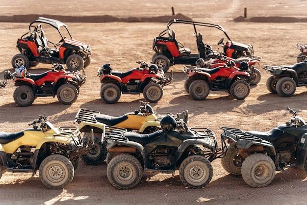 Duża kolejka quadów i buggy stoi pośrodku piaszczystej pustyni?
