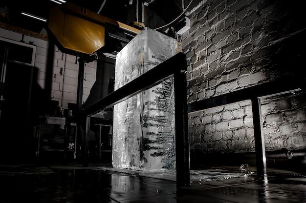 Duża kostka lodu stoi na podłodze w zakładzie produkcji lodu