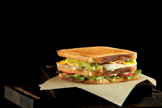 Duża kwadratowa kanapka z warzywami i kurczakiem na papierze kraft. zbliżenie, miejsce na tekst.