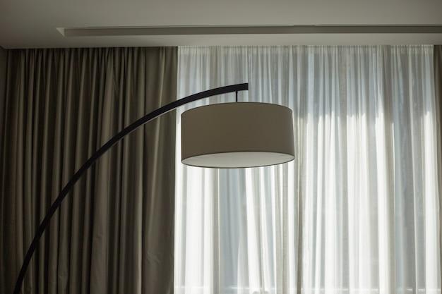 Duża lampa podłogowa na tle białych zasłon vintage torchere