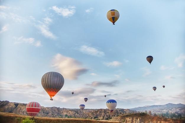 Duża liczba balonów lata rano w promieniach nieba