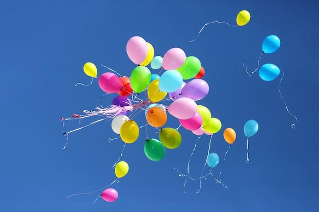 Duża liczba kolorowych balonów na tle błękitnego nieba. dekoracje świąteczne