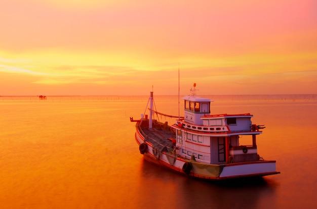 Duża łódź rybacka wychodząca na rejs o zachodzie słońca