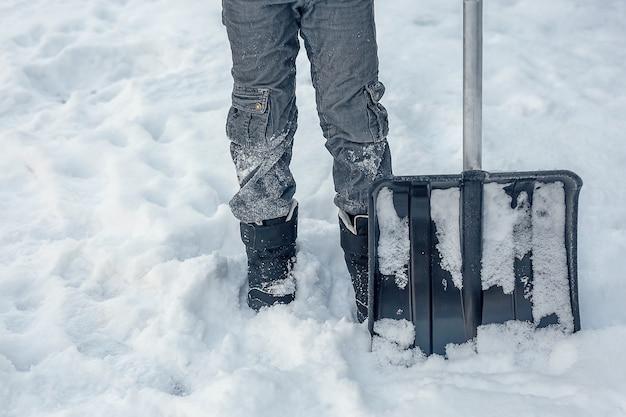 Duża łopata do śniegu obok mężczyzny w czarnych zimowych butach.