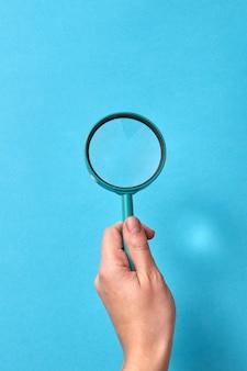 Duża lupa w dłoni kobiety. koncepcja wyszukiwania i studiów.